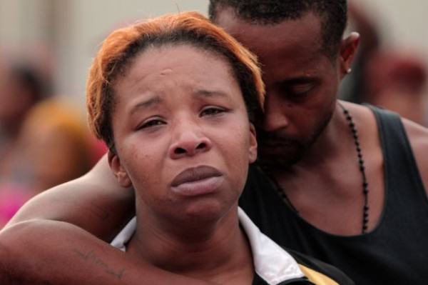 Huy Mach, hmach@post-dispatch.com. caption: Lesley McSpadden is comforted by her husband, Louis Head, after her 18-year-old son was shot and killed by police earlier in the afternoon in the 2900 block of Canfield Drive on Saturday, Aug. 9, 2014, in Ferguson. Head is the step-father.